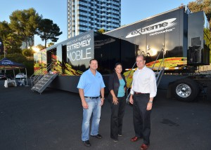 Pictured outside the Extreme Networks Mobile Lab are (L-R)  Mike Braico,  IMT EVP of Sales; Madeline Hazely, IMT Marketing Coordinator; and Dick Gertridge,  Extreme Networks Western Region Sales Director.  Photo by David Goggin.