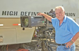 Bill McKechney, Vice President of Engineering at F&F Productions, stands with FUJINON XA99x8.4 ultra-wide lens in front of new GTX-17 mobile unit.