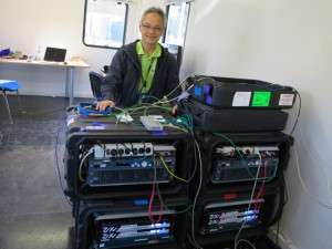 Tom Sahara, Turner Sports, senior director, IT and remote operations, with the two racks of equipment at the center of PGA.com's coverage of the Ryder Cup.