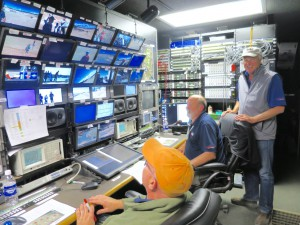 Scott Lambert (left), Earl Freeman (center), and Peter Larsson (back) inside the BSI production trailer that is managing wireless cameras and microphones at the U.S. Open